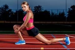 Atleta attraente della giovane donna che allunga le gambe sullo stadio Fotografie Stock Libere da Diritti