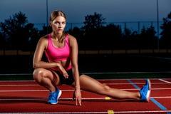Atleta attraente della giovane donna che allunga le gambe sullo stadio Fotografia Stock