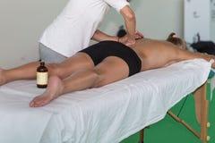 Atleta Back Massage após a atividade da aptidão - bem-estar e esporte imagem de stock