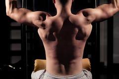 Atleta bello Doing Pull Ups - Chin-UPS dell'uomo nella palestra fotografia stock libera da diritti