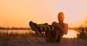 Atleta bonito novo da mulher que pratica na praia que faz exercícios para os músculos do Abs no por do sol Torção dentro video estoque