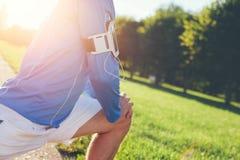 Atleta in camicia blu che fa allungando riscaldamento prima dell'allenamento nel parco Immagine Stock Libera da Diritti