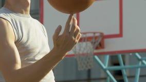 Atleta caucásico muscular que hace girar dominante el baloncesto en su finger, truco metrajes
