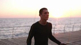 Atleta caucasico che salta sopra l'aria aperta della corda di salto negli abiti sportivi neri Il Sun splende sui precedenti seasi video d archivio
