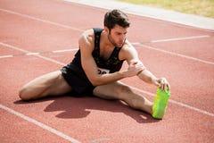 Atleta che fa allungando esercitazione Immagine Stock