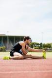 Atleta che fa allungando esercitazione Fotografie Stock Libere da Diritti