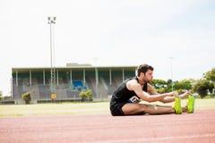 Atleta che fa allungando esercitazione Fotografia Stock