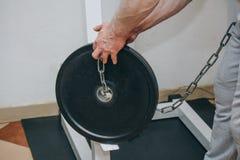Atleta che fa esercizio con peso sulla cinghia di vita nel centro di addestramento strumenti di formazione nel primo piano della  fotografia stock