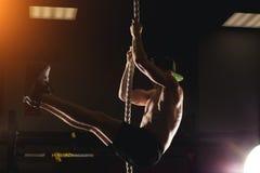 Atleta che fa esercizio di salita della corda di forma fisica nell'allenamento della palestra di forma fisica Fotografia Stock Libera da Diritti