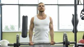Atleta che fa esercizio per il bicipite con il bilanciere Giovani treni muscolari dell'uomo alla palestra Immagini Stock