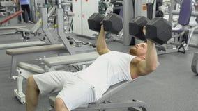 Atleta che fa esercizio per il petto con le teste di legno Giovani treni muscolari dell'uomo alla palestra Fotografia Stock Libera da Diritti