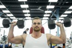 Atleta che fa esercizio per le spalle con le teste di legno che si siedono su un banco Giovani treni muscolari dell'uomo alla pal immagine stock libera da diritti