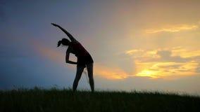 Atleta che fa gli esercizi su una siluetta di tramonto di una ragazza stock footage