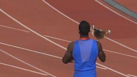Atleta che indica all'arena di sport che è vincitore, baciante la tazza attesa da tempo archivi video