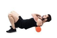 Atleta che massaggia i muscoli dorsali superiori con il rullo della schiuma fotografie stock libere da diritti