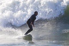 Atleta che pratica il surfing sulla spiaggia di Santa Cruz in California Immagini Stock