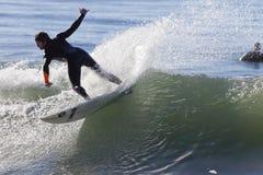 Atleta che pratica il surfing sulla spiaggia di Santa Cruz in California Fotografia Stock