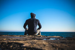Atleta che prende rottura che si siede sulle rocce con l'orizzonte di mare Immagini Stock