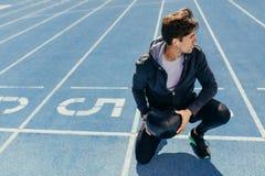 Atleta che si siede sulla pista corrente con una palla medica Immagine Stock