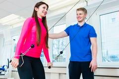 Atleta che utilizza l'attrezzatura di allenamento nella palestra ed ottenendo assistenza dall'istruttore Immagine Stock Libera da Diritti