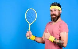 Atleta chwyta tenisowy kant w ręce na błękitnym tle Tenisowy sport i rozrywka Tenisowego klubu pojęcie Mężczyzna brodaty zdjęcia stock