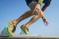 Atleta com os tênis de corrida do ouro que começam uma raça Foto de Stock