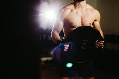 Atleta com a placa do peso no gym imagens de stock royalty free