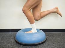 Atleta com um tornozelo torcido que faz exercícios do reforço e do equilíbrio em uma bola do bosu fotografia de stock royalty free