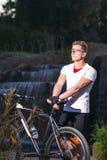 Atleta con il mountain bike che posa contro la cascata all'aperto immagini stock libere da diritti