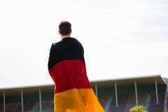 Atleta con la bandera alemana envuelta alrededor de su cuerpo Imágenes de archivo libres de regalías