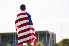 Atleta con la bandera americana envuelta alrededor de su cuerpo Imágenes de archivo libres de regalías