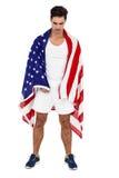 Atleta con la bandera americana envuelta alrededor de su cuerpo Fotos de archivo