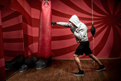 Atleta con la maglia con cappuccio che risolve alla palestra di pugilato, preparantesi per la lotta Fotografia Stock