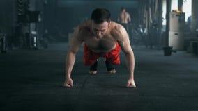 Atleta con un bello corpo e un torso nudo che fanno esercizio di spinta-UPS sul pavimento alla palestra 4K ha sparato in un tono  archivi video