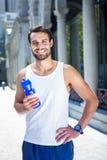 Atleta considerável de sorriso que guarda a garrafa Imagens de Stock