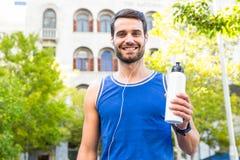 Atleta considerável que sorri e que guarda a garrafa Foto de Stock