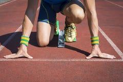 Atleta Crouching en los bloques el comenzar corrientes de la pista Fotografía de archivo