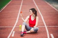 Atleta da jovem mulher no estilo de vida ostentando do estádio, sentando-se na trilha, tomando a foto do selfie em um smartphone fotos de stock