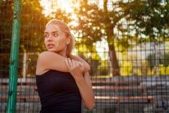 Atleta da jovem mulher que aquece-se antes de correr no sportsground no verão Estilo de vida ativo imagem de stock