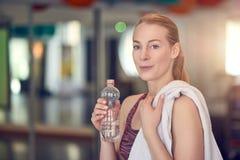 Atleta da jovem mulher que bebe a água engarrafada Imagem de Stock Royalty Free