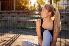 Atleta da jovem mulher que tem o resto após a corrida no sportsground no verão Menina que refrigera fora na manhã imagens de stock royalty free