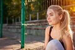 Atleta da jovem mulher que tem o resto após a corrida no sportsground no verão Menina que refrigera fora na manhã foto de stock