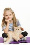 Atleta da menina da criança de seis anos que senta-se em um tapete com o gato em seu regaço Fotografia de Stock