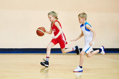 Atleta da menina e do menino no uniforme que joga o basquetebol Fotografia de Stock Royalty Free