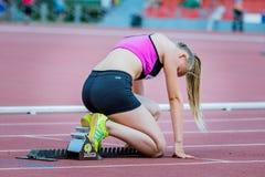 Atleta da menina na posição começar sobre uma trilha atlética Fotografia de Stock Royalty Free