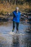 Atleta de la chica joven que cruza un río de la montaña Imagen de archivo libre de regalías
