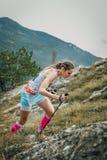 Atleta de la muchacha con los bastones que van cuesta arriba Fotos de archivo