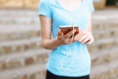 Atleta de la muchacha con un teléfono en sus manos, el escuchar de funcionamiento la música, entrenamiento de la mañana Foto de archivo libre de regalías
