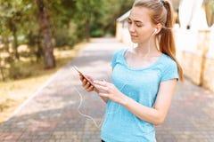 Atleta de la muchacha con un teléfono en sus manos, el escuchar de funcionamiento la música, entrenamiento de la mañana Imagenes de archivo