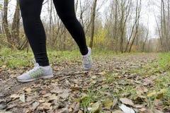 Atleta de la muchacha en las zapatillas de deporte y las polainas que corren a lo largo de la trayectoria Fotografía de archivo